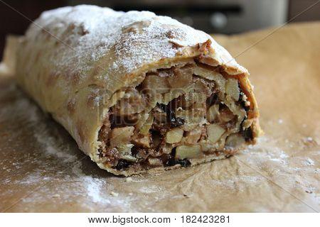 Cut piece of apple strudel. Half loaf of fresh apple strudel on baking paper. Homemade apple strudel with raisins.
