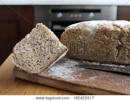 Bread lof with a cut piece in the kitchen. Homemade rye bread cut into pieces on the wooden board.