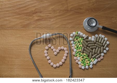 Black Stethoscope and pill on wood table with selective and soft focus.