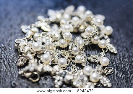 Necklace of silver with pearls lying in the center of the frame on a dark background with a pronounced texture. The necklace glitters and sparkles, attracts attention