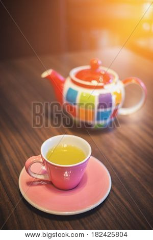 Close focus on pink ceramic teacup with green tea and colorful pot on table. Soft warm light from top corner.