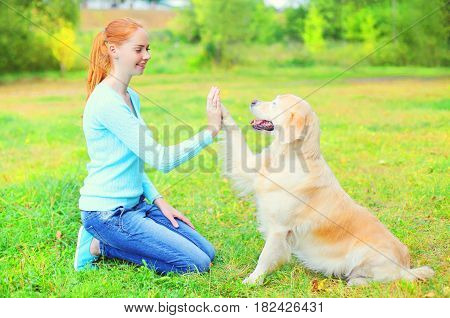 Happy Owner Woman Is Training Golden Retriever Dog On The Grass In A Park