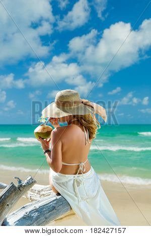 Woman in bikini with sunhat at tropical beach