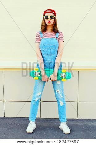 Fashion Pretty Cool Girl Wearing A Denim Jumpsuit With A Skateboard Over White Background