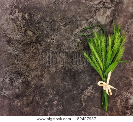 Cute bouquet of spikelets with a cute bow on dark marble stone table with copy space. Summer cozy composition rustic holiday concept. Flat lay top view space for text