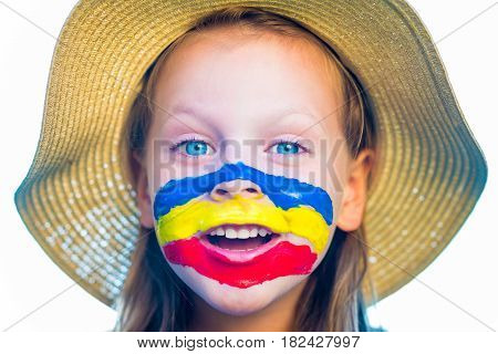 Laughing little girl in straw hat with painted face having fun. Isolated on white