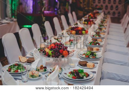 Beautifully decorated catering banquet table with different food snacks and appetizers with sandwich, caviar, fresh fruits
