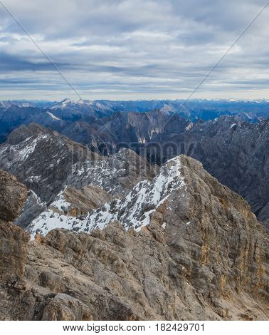 Beautiful vibrant view on mountain Zugspitze (highest mountain of Germany) with mountain lake in foreground, landscape of Alpine Alps mountain view from Zugspitze, top peak of Germany