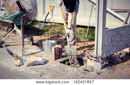 Worker on laying the foundation with a mixer and shovel.