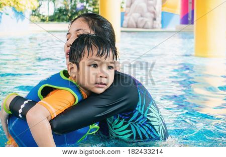 Women is saving a boy from water swimming pool.