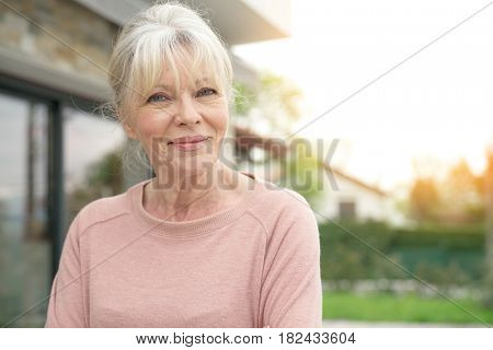 Portrait of blond senior woman sitting in front of new house