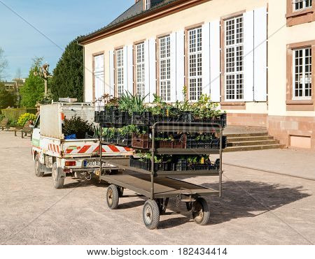 STRASBOURG FRANCE - APR 12 2016: Gardener van with carriage trailer transporting toward destination new fresh flowers tree and bushes for the green spring park