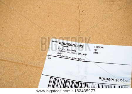 PARIS FRANCE - APR 9 2017: Amazon Japan Amazon.co.jp logotype printed on cardboard box white address line slip seen from above. Amazon Inc is the an American electronic e-commerce company