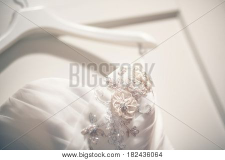 Beautiful white dress of bride, detail of wedding dresses of satin on hanger, vintage dress to marry