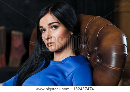 A Girl In A Blue Dress Is Sitting In A Chair.