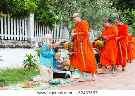 Luang Prabang, Laos - Jun 15 2015: Buddhist Alms Giving Ceremony In The Morning. The Tradition Of Gi