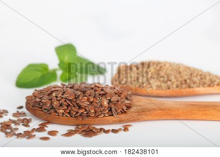 Organic linseeds and ground flaxseeds in small wooden spoons. Healthy vegan food.