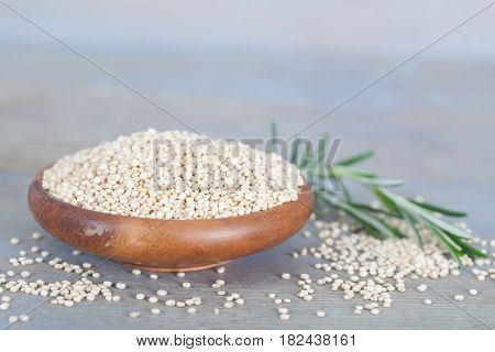 Wooden bowl full of healthy white quinoa seeds. Healthy vegan food.