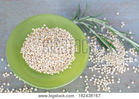 Raw white quinoa seeds in green bowl. Healthy food.