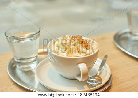 A cup of coffee latte on a tray with glass on water and teaspoon in fron of the window. Copy space.