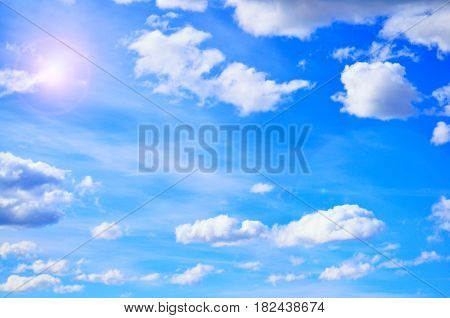 Blue sky background with white clouds in the sky lit by sunny light in good weather - sky background with clouds in the sky. Beautiful sky landscape. Blue sky landscape