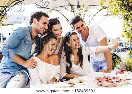 Group of young beautiful people sitting in a restaurant and taking a selfie while smiling