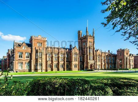 The Queen's University of Belfast with a grass lawn, tree branches and a hedge in sunset light