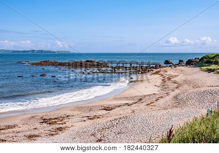 Sand beach with small wooden bridge at Pan's Rock near Ballycastle in County Antrim and far view of Rathlin Island, Northern Ireland, UK