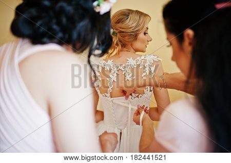 Fashionable Bridesmaids On Pink Dresses Helped Wear Bow On Back Of Wedding Dress Bride. Morning Wedd