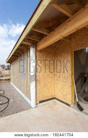 Modern frame energy efficient house under construction with membrane coverings roof shingles and insulation materials