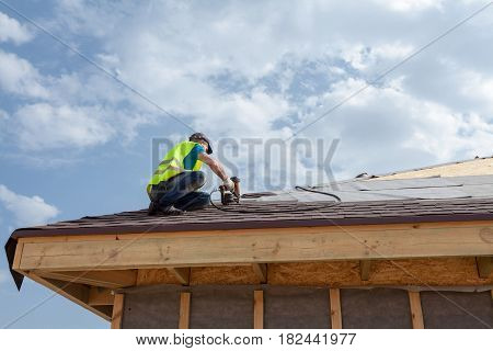 Construction worker putting the asphalt roofing (shingles) with nail gun on a new frame house