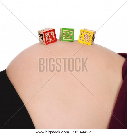 colourful alphabet blocks resting on bare pregnant belly isolated on white