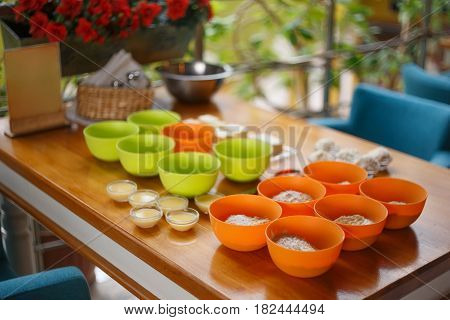 Cookery Set Of Orrange And Green Cups With Flour And Condensed Milk Standing At Light Brown Wooden T