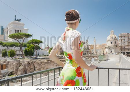 Back view of tourist woman is looking ahead on historical place