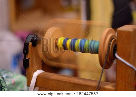 Spool of a spinning wheel rotates with colorful wool quickly