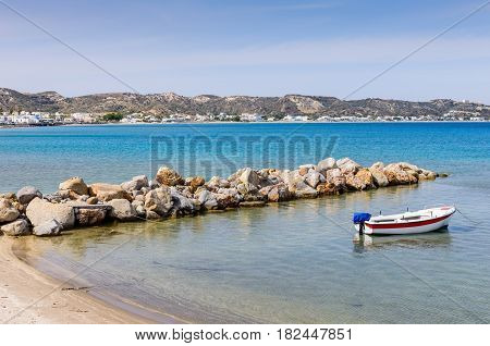 Beautiful sandy beach with fishing boat in a sunny summer day, Kefalos village, Kos island, Dodecanese, Greece