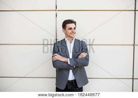 Businessman Standing With Crossed Hands Outdoors With Office Buildings In Background