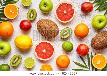 Citrus sliced fruits background flat lay, healthy vegetarian organic food, antioxidant detox nutrition diet. Tropical summer assortment mix grapefruit, coconut, orange, apple, mandarin, sliced kiwi