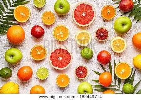 Citrus sliced harvest fruits background flat lay, helthy vegetarian organic food, antioxidant detox nutrition diet. Tropical summer assortment mix grapefruit, coconut, orange, apple, mandarin