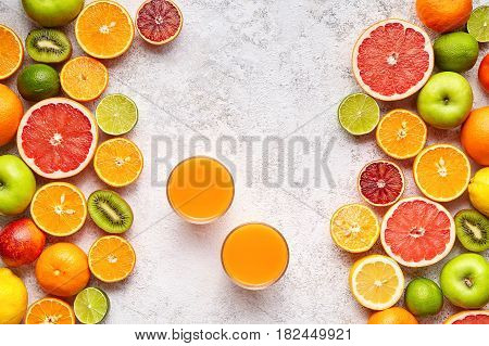 Fresh juice vitamin c drink in citrus fruits background flat lay, healthy lifestyle vegetarian organic antioxidant detox diet beverage. Tropical summer assortment grapefruit, orange, apple