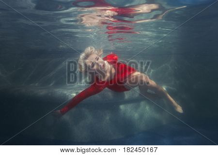 Blond woman under the water in the pool wearing a red dress.