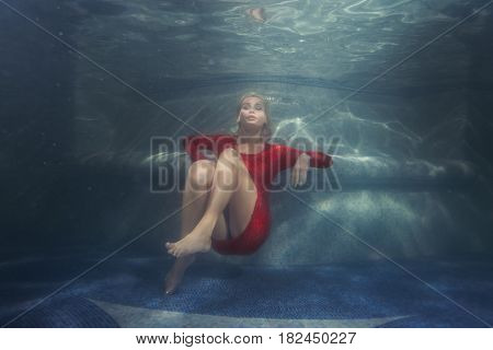 Woman dives under the water in a red dress.