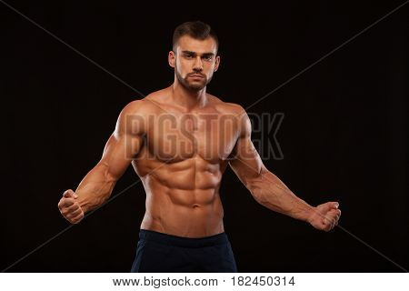 Strong Athletic Man Fitness Model Torso showing six pack abs. isolated on black background with copyspace.
