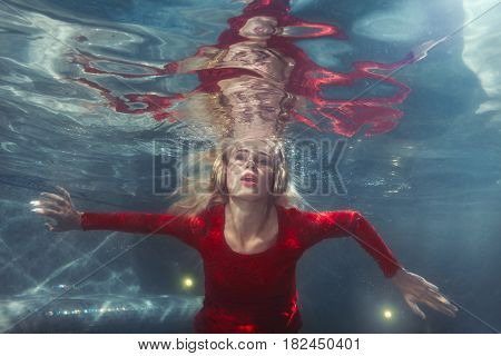 Woman listens to music under the water in the pool.