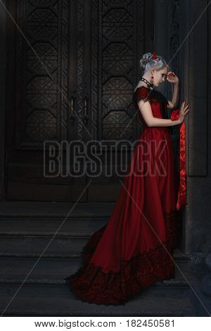 Sad woman in retro style on the steps of a fairytale castle.