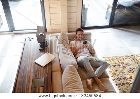 Full-length shot of cheerful man with phone lying on soft couch