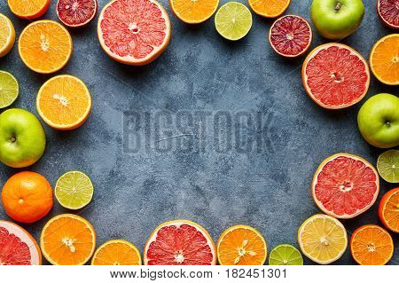 Fruits sliced mix frame flat lay on blue concrete background blank copy design space, healthy vegetarian organic food, antioxidant detox diet. Tropical summer mix grapefruit, orange, apple mix