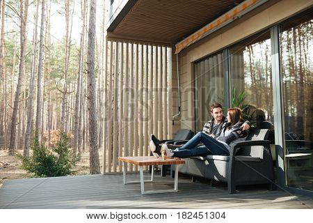 Young handsome man and his woman hugging and sitting on coach near house