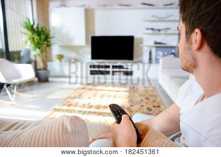 Young man with remote controller sitting against blank scree of TV in living room