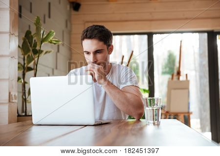 Yong brunette man sitting and thinking near laptop in light living room